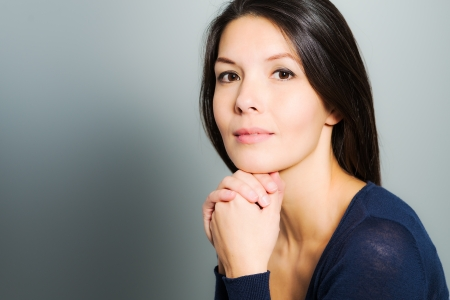 Thoughtful attractive woman with a serene face and enigmatic smile standing with her hand to her chin looking pensively at the camera