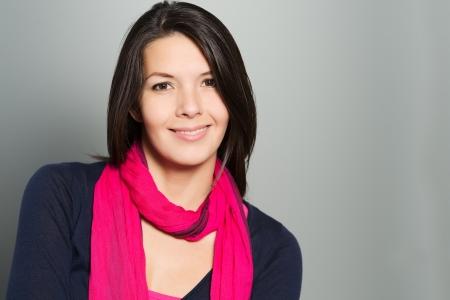 Mooie jonge brunette vrouw met een mooie warme glimlach rust haar kin op haar hand op zoek direct op de camera Stockfoto