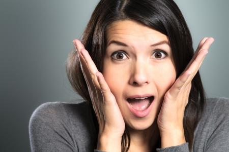 Aantrekkelijke vrouw schreeuwen in de terreur met haar handen op haar wangen, mond open en bang grote ogen, close-up gezicht portret Stockfoto