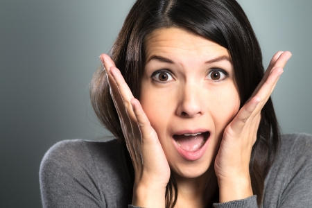 Attractive woman screaming in terror with her hands to her cheeks, mouth open and frightened wide eyes, close up facial portrait