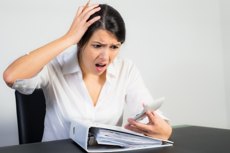 dismay: Businesswoman sitting at her desk with a large office binder looking at her calculator in horror or dismay with her mouth open in shock Stock Photo