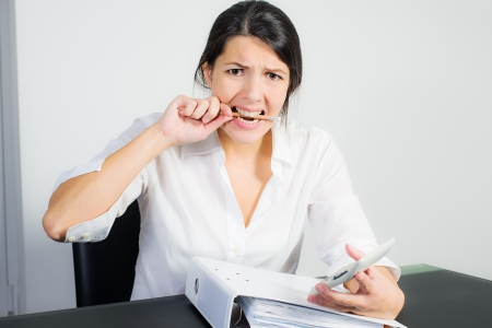 distraught: Businesswoman with a distraught expression biting her pen in frustration, worry or anger as she sits at her desk holding a calculator in her hand