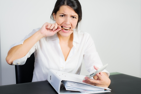 Businesswoman with a distraught expression biting her pen in frustration, worry or anger as she sits at her desk holding a calculator in her hand photo