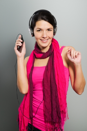 downloaded: Beautiful trendy woman in a colourful magenta summer dress and scarf listening to music on her headphones from the tunes downloaded onto her storage device