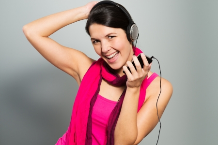 vivacious: Beautiful vivacious woman listening to music on headphones connected to a handheld electronic storage device as she stands laughing at the camera