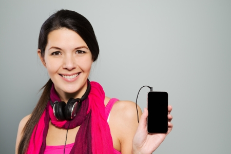 downloaded: Charming attractive young woman in a stylish trendy pink outfit presenting a music storage device holding it up in her hand for the attention of the viewer