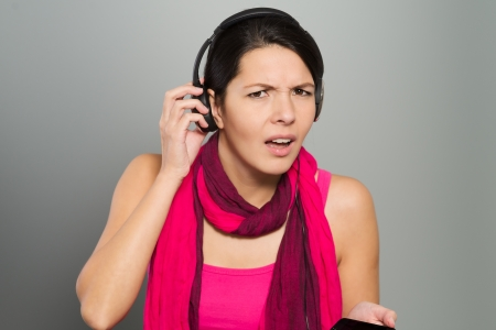 puzzlement: Beautiful young woman in a stylish pink outfit with a scarf listening to music struggling to hear something that is being said to her as she raises the earphone from her ear with a frown of puzzlement