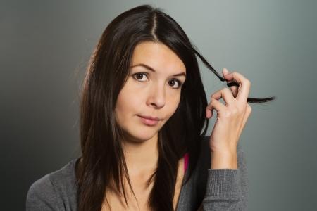 mujer pensativa: Mujer joven atractiva pensativa girando su cabello largo Morena alrededor de sus dedos mientras mira a la cámara con una expresión pensativa mirada