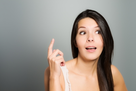 either: Attractive young woman signalling with her index finger as she either tries to attract attention to herself or as she raises her finger in admission by identifying herself, on a grey studio background Stock Photo