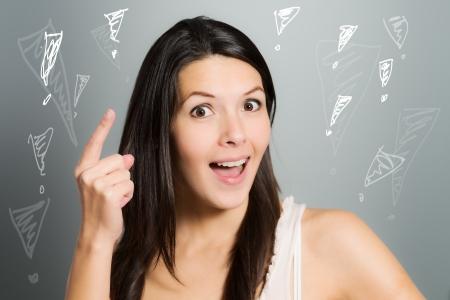 signalering: Aantrekkelijke jonge vrouw signalering met haar wijsvinger dat ze een oplossing voor een bepaald probleem heeft gevonden, op een grijze achtergrond studio