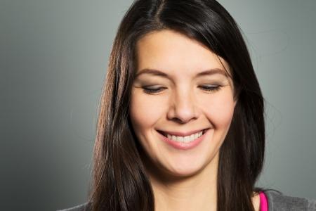 ojos cerrados: Mujer contenta feliz con una sonrisa con dientes sonriendo con los ojos cerrados, cerca retrato facial en un estudio de fondo gris