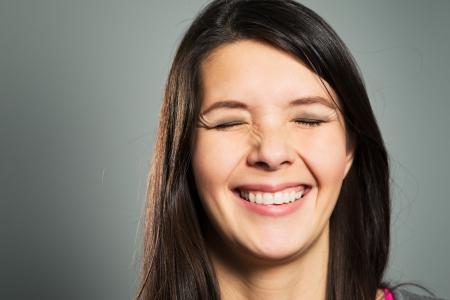 彼女の目を閉じた、クローズ アップ灰色のスタジオの背景の顔の肖像画と晴れやかな歯を見せる笑顔で幸せ満足している女性