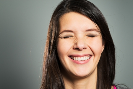 Happy pleased woman with a beaming toothy smile with her eyes closed, close up facial portrait on a grey studio background