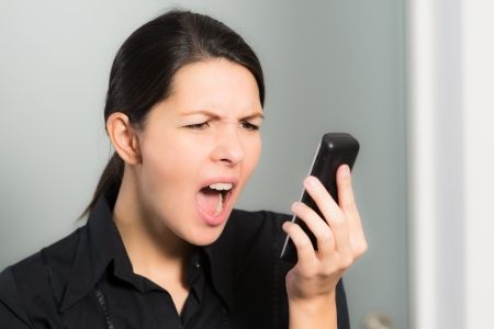 Portrait of a brunette Caucasian young woman screaming while looking at her mobile phone, symbol of stress and negative emotions, on gray background photo