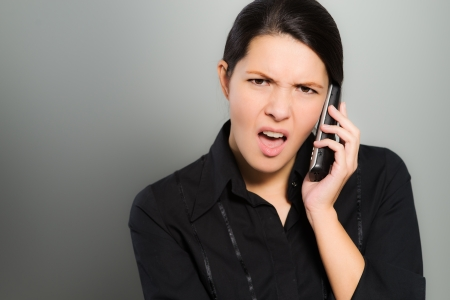 frown: Nervous beautiful young woman chatting on her mobile phone and looking at the camera with a confused expression and frown, over a grey studio background