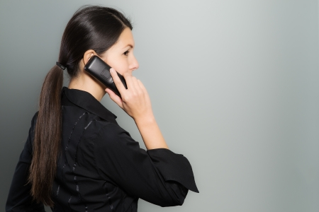surreptitious: Secretive businesswoman talking on her mobile phone standing facing away from view while glancing back surreptitiously to ensure her privacy, on a gray background with copyspace