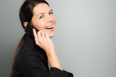 mirth: Attractive young woman with long brunette hair standing sideways laughing with delight while chatting on her mobile phone over a gray background with copyspace Stock Photo