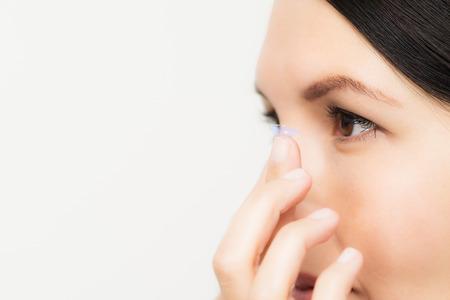 Vrouw om een wegwerp plastic contactlens plaats in haar oog Stockfoto