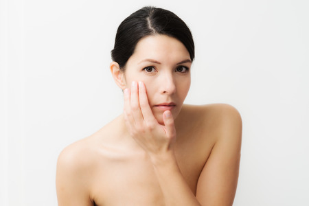 Portrait einer sexy Brünette kaukasischen junge Frau in den Spiegel schauen, beobachten Gesichtsfalten, erste Zeichen der Hautalterung Standard-Bild