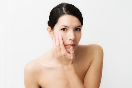 arrugas: Retrato de una morena de raza caucásica sexy mujer joven mira en el espejo, observando las arrugas faciales, primer signo de envejecimiento Foto de archivo