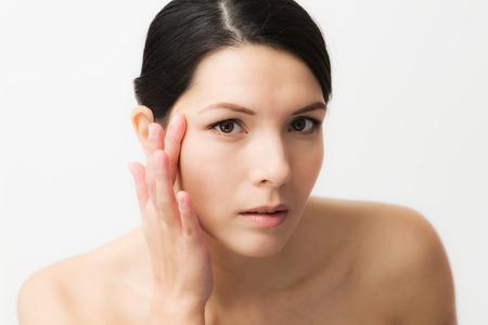 Portret van een sexy brunette blanke jonge vrouw in de spiegel kijken, observeren van rimpels, eerste tekenen van het ouder worden