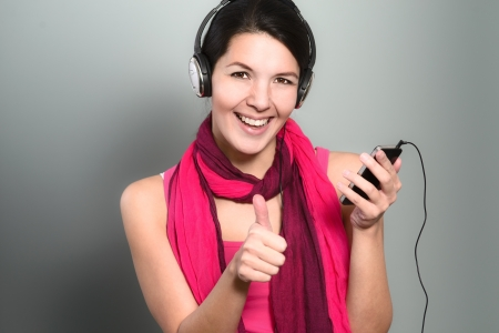 Beautiful trendy woman in a colourful magenta summer dress and scarf listening to music on her headphones and giving a thumbs up to her music photo