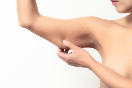 arm muscles: Woman testing the flabby muscle under her arm pulling it down with her hand as she checks for muscle tone or weight gain