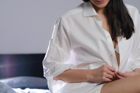 Mujer joven a desabrocharse la camisa blanca mientras se prepara para ir a la cama por la noche con una tentadora idea de su sostén visible Foto de archivo - 25358202