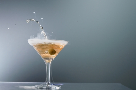 wafting: Smoking martini cocktail in a conical glass with wafting vapour and splashing droplets from a falling olive for a dramatic effect over a grey background