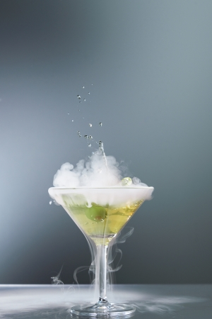Smoking martini cocktail in a conical glass with wafting vapour and splashing droplets from a falling olive for a dramatic effect over a grey background