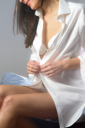 Young woman unbuttoning her white shirt as she prepares to go to bed in the evening with a tantalising glimpse of her bra visible photo