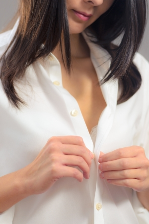 Smiling young woman with long brunette hair getting dressed buttoning up her clean white shirt, torso view Stock Photo