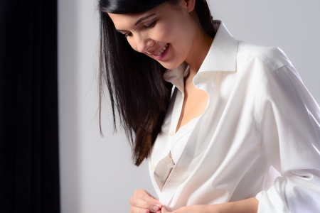 tantalising: Young woman unbuttoning her white shirt as she prepares to go to bed in the evening with a tantalising glimpse of her bra visible
