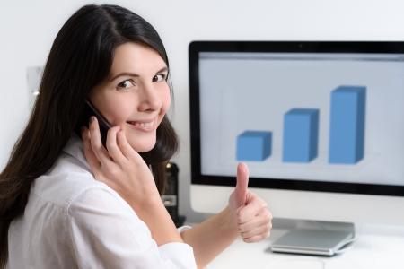 Gelukkig vrouwelijke beambte zitten aan het bureau en praten met de telefoon het geven van een thumbs-up