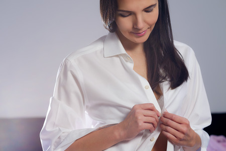 changing clothes: Attractive young woman with long brunette hair standing unbuttoning her clean white shirt as she undresses in the evening