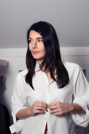 Attractive young brunette woman standing dressing in a walk in dressing room buttoning up her clean white shirt while looking thoughtfully off to the side