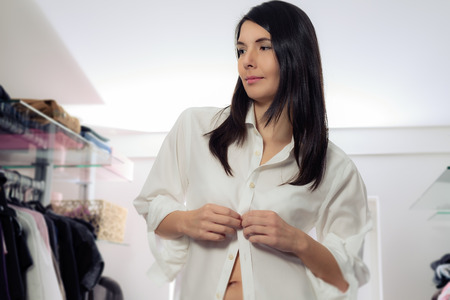 Attractive young brunette woman standing dressing in a walk in dressing room buttoning up her clean white shirt while looking thoughtfully off to the side photo