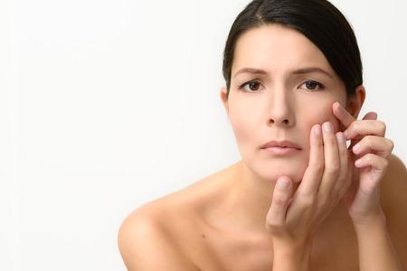 Schöne Frau Überprüfung ihrer Teint für Hautunreinheiten, wie sie in den Spiegel blickt mit ernster Miene Lizenzfreie Bilder