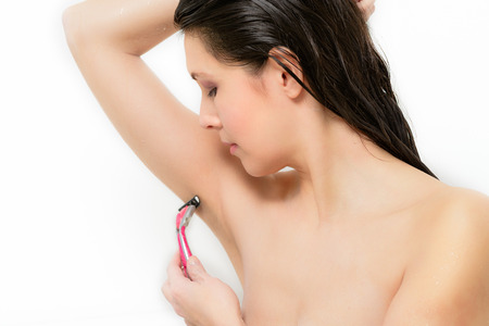 armpit hair: Beautiful young woman shaving her armpit with a razor to remove unsightly hair, isolated on a white background Stock Photo