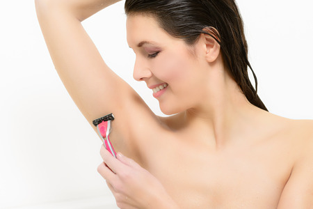 Beautiful young woman shaving her armpit with a razor to remove unsightly hair, isolated on a white background photo