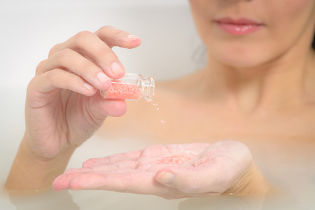 soaking: Woman enjoying a rejuvenating therapeutic aromatherapy bath at a spa soaking in the warm soapy water pouring bath salt crystals into her hand