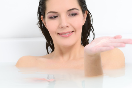 soaking: Woman enjoying a rejuvenating therapeutic aromatherapy bath at a spa soaking in the warm soapy water