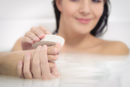 Woman relaxing in a hot soapy bath using a pumice stone to exfoliate her feet 스톡 콘텐츠