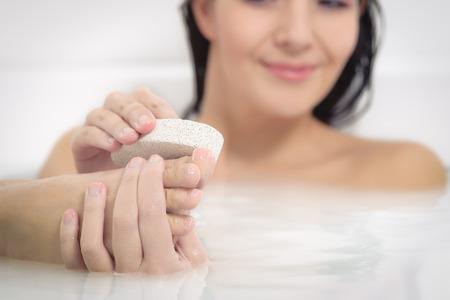 Woman relaxing in a hot soapy bath using a pumice stone to exfoliate her feet Foto de archivo