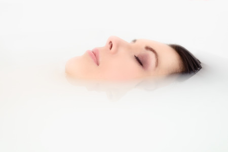 immersed: Blissful beautiful young woman pampering herself soaking in a hot bath with just her face visible above the soapy water Stock Photo