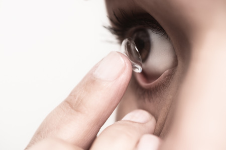 consumable: Woman about to place a disposable plastic contact lens in her eye Stock Photo