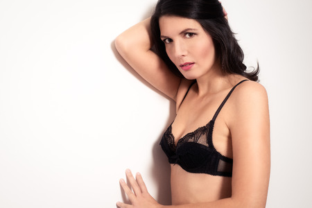 submissive: Frightened young woman in a black bra leaning against a wall looking across at the camera with an apprehensive look as she shields herself from mental abuse in the home Stock Photo