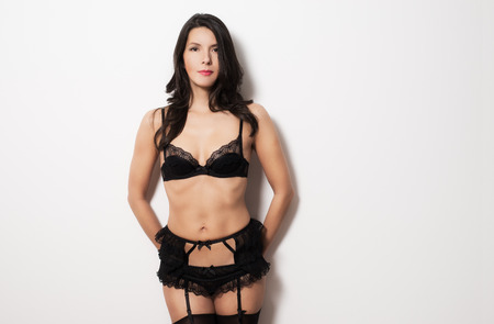 Beautiful woman wearing sexy black underwear with a lacy bra, suspender and stockings standing against a wall with her hands behind her in a tantalising pose showing off her shapely bare body photo