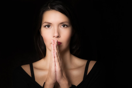 faithful: Dark evocative portrait of a spiritual young woman praying with her hands clasped and an intent look in her eyes