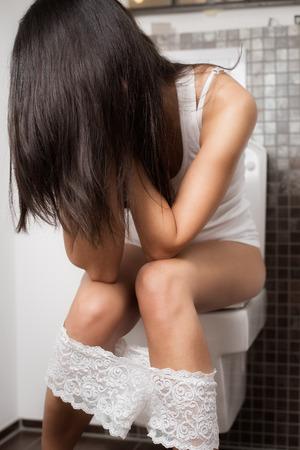 diarrea: Mujer joven de ir al baño sentado en el recipiente con la cabeza entre las manos y el pelo marrón largo que cubre la cara con las bragas de encaje alrededor de sus piernas